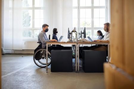 Businessman in wheelchair working at his desk