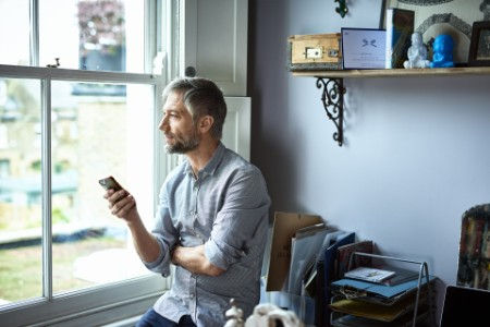A man sitting with phone and looking through window