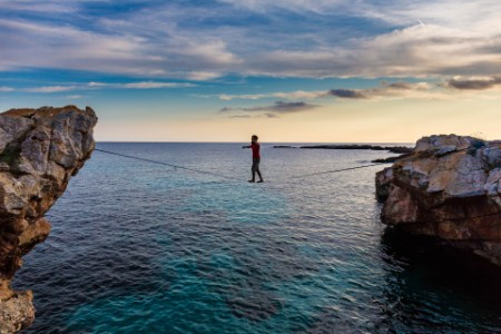 Man practicing slackline over the sea