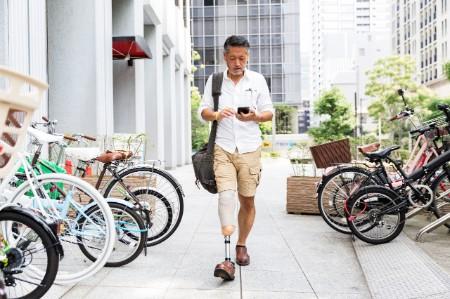 man prosthetic leg walking checking phone