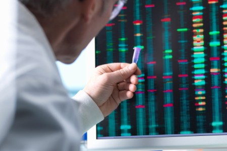 Scientist holding dna sample results on computer screen