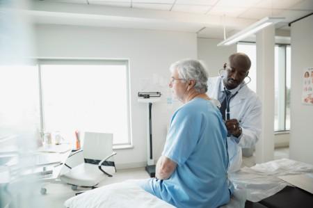 doctor checking senior man۪s back in examination room