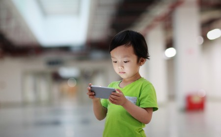 young boy looking at smartphone