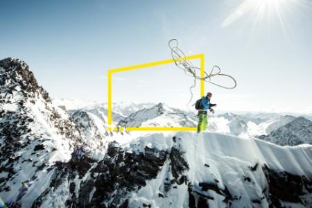 Homem a atirar corda de escalada no topo de montanha com neve