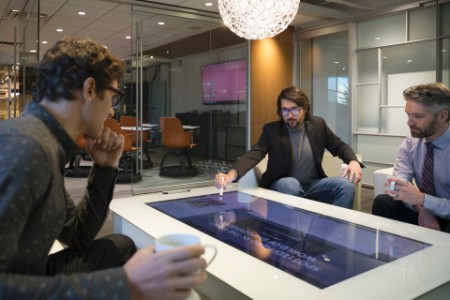 Business-persons meeting over interactive touch table