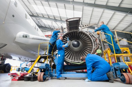 Workers installing a jet engine