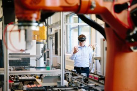 Insinööri työskentelee ar-kuulokkeilla tuotantolinjalla