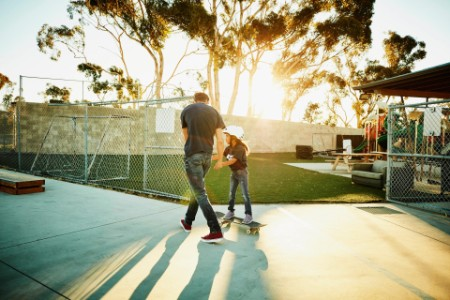 Skateboard instructor helps child
