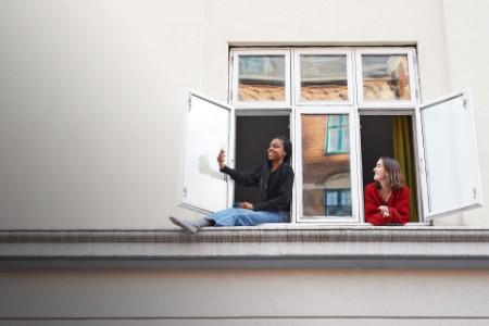 Woman taking selfie in window