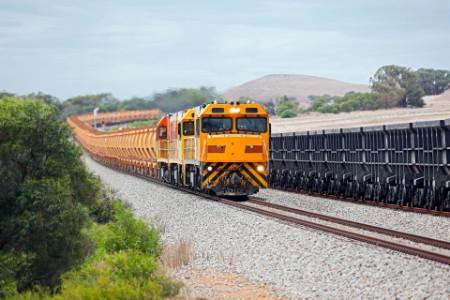 Loaded hematite iron ore train passing empty magnetite wagons