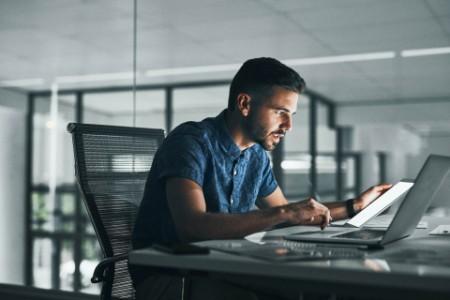 Businessman working night desk office laptop tablet