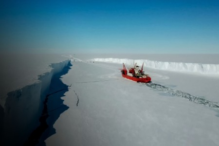 Ice breaking ship cutting passage throught sea ice