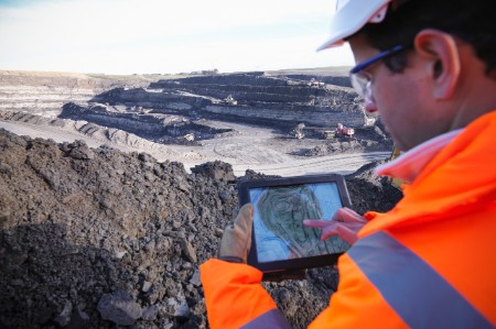 Ecologist using digital tablet surveying surface coal mine site