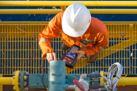 Offshore oil rig worker calibrating coriolis digital flow meter