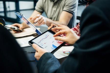Team meeting looking data digital tablets