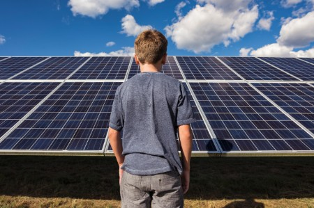 Boy stands in front of blue solar panels