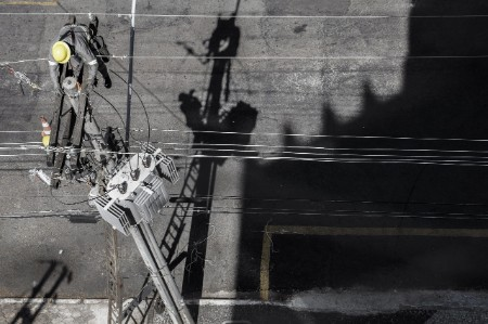 Engineer works on an electric pylon over a road