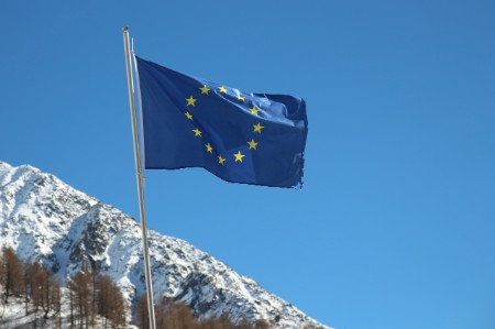 European Union flag flying in front of a snowcapped mountain