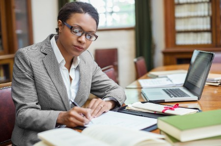 Woman lawyer sits at desk working with papers and a laptop