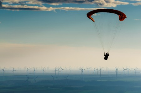 Paraglider flies through blue sky towards numerous wind turbines in the distance