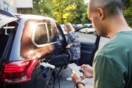 Man on smartphone waiting as electric car charges