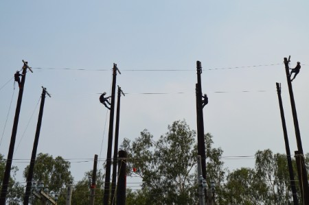 Four Engineers working up high on electricity pylons