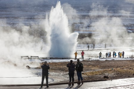 People stand and watch geysers erupt in Iceland