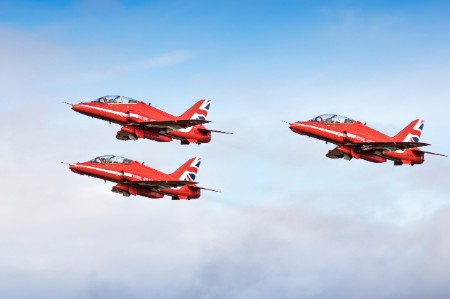 Three Royal Air Force red arrows flying in blue sky