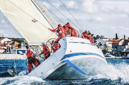 Crew sail a yacht through the sea