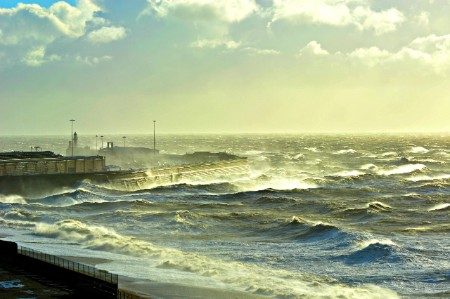Stormy seas and waves hit a jetty and coastal beach