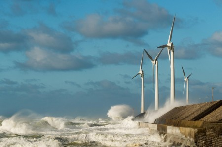 High waves splash coastal wind turbines