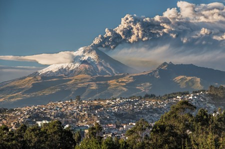 Cotopaxi volcano erupting in the distance behind a hilly town