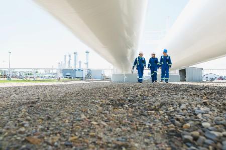 Engineers walk below two large gas pipes