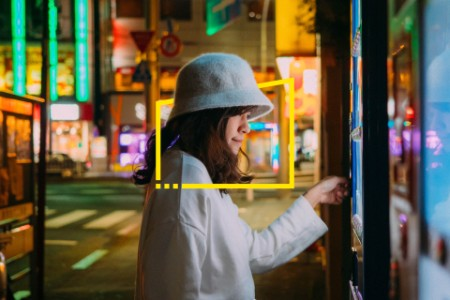 Asian woman selecting some drink at vending machine