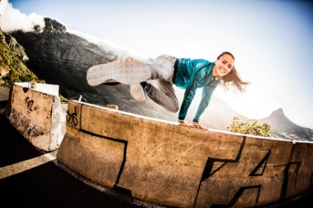 Breakdancing girl doing parkour jump over wall