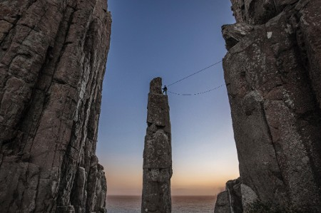 Climber standing on top on the Totem Pole sea stack in Tasmania, Australia