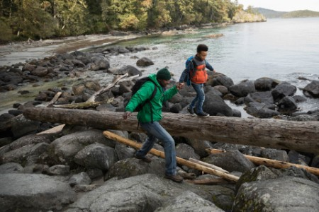 Father son crossing rocks fallen log rugged beach