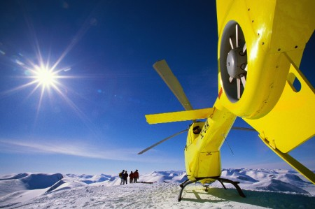 Yellow helicopter on a snow-covered mountain top