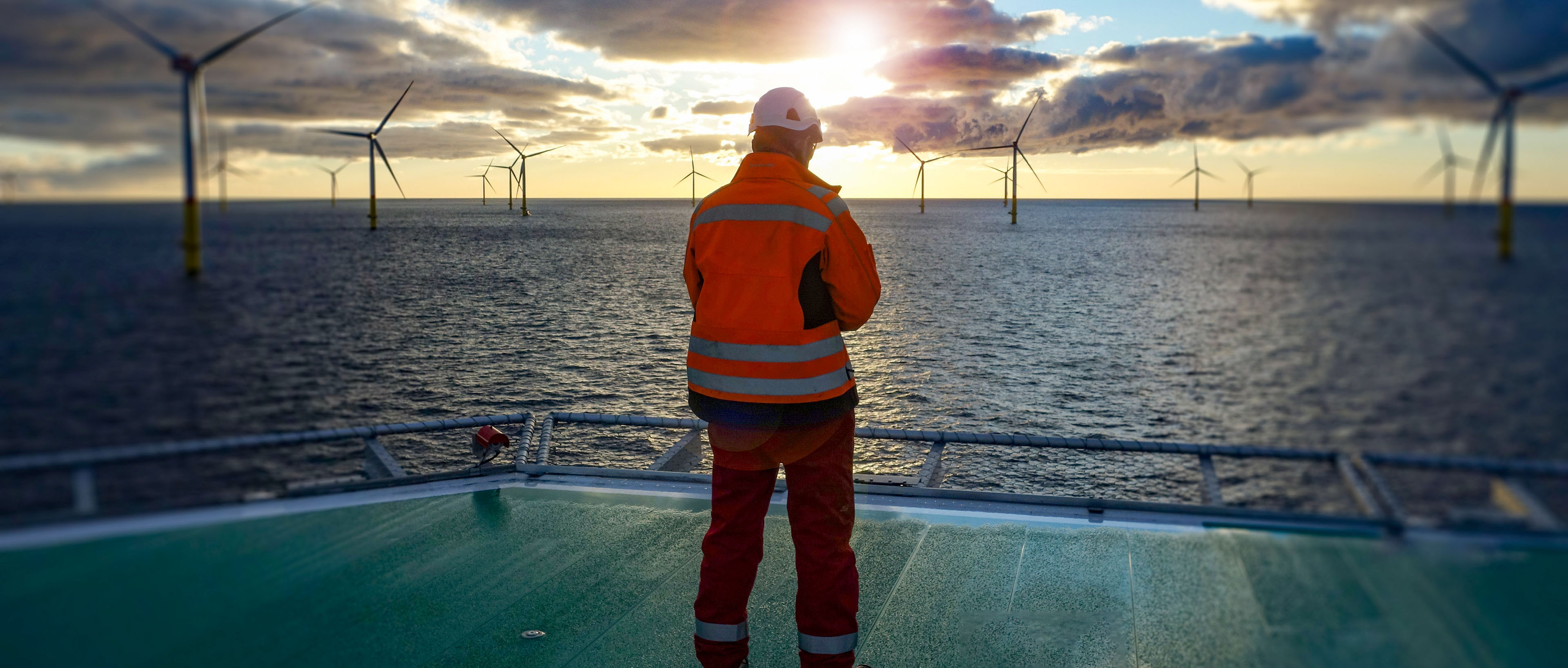 Offshore worker standing on helipad with wind-turbines behind him in sunset