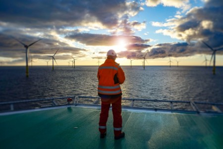Offshore worker standing on helipad with wind turbines behind him in sunset