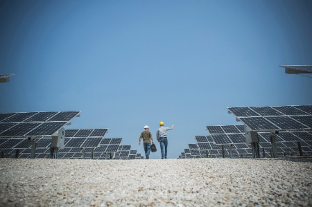 Two technicians walk through a solar panel plant under a blue sky