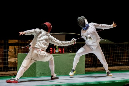 Two men fencing sports arena