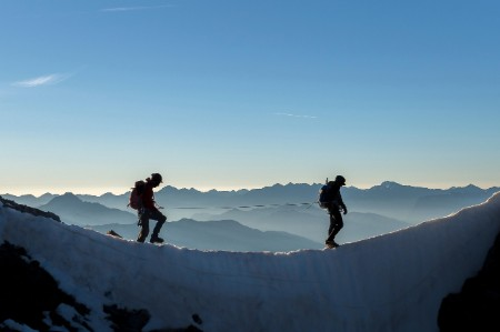 Two mountaineers roped together walk across an iced ridge