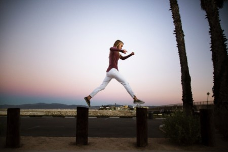 Woman jumping pole to pole pier