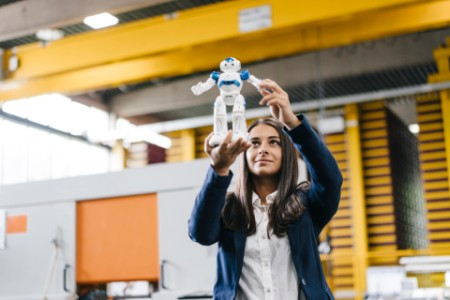 Woman working in distribution warehouse looking at toy robot