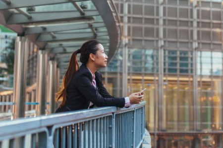 Business woman standing on pedestrian bridge in hong kong