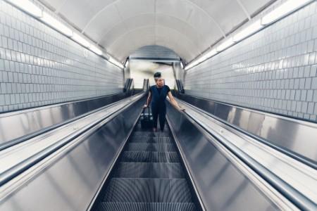 Mujer de negocios con maleta saliendo de la estación de metro