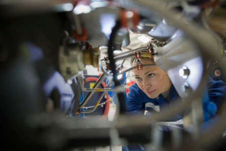 Female helicopter mechanic examining wires