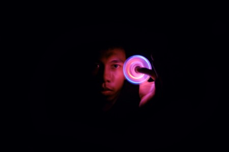 Man with illuminated fidget spinner in dark room