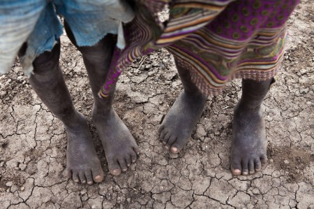 african people stand barefooted dry cracked ground